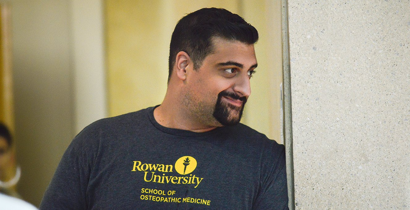 A smiling RowanSOM student wearing an SOM t-shirt.