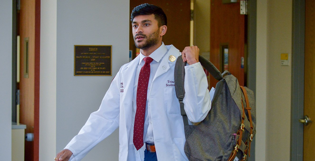 First-year RowanSOM medical student, Trinava Roy, walks through Rowan Medicine building with his back pack.