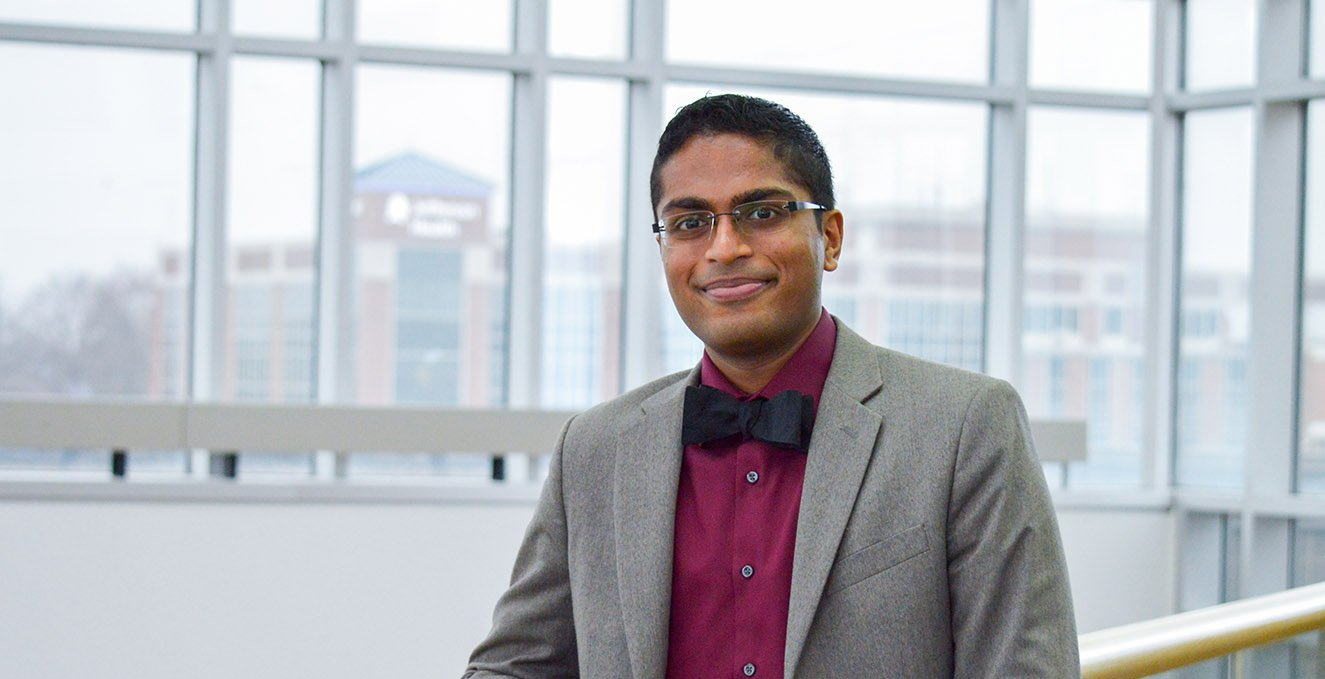 Fourth-year RowanSOM medical student, Chan Bivishi, on the third floor of the Atrium, with Jefferson Health in the background.