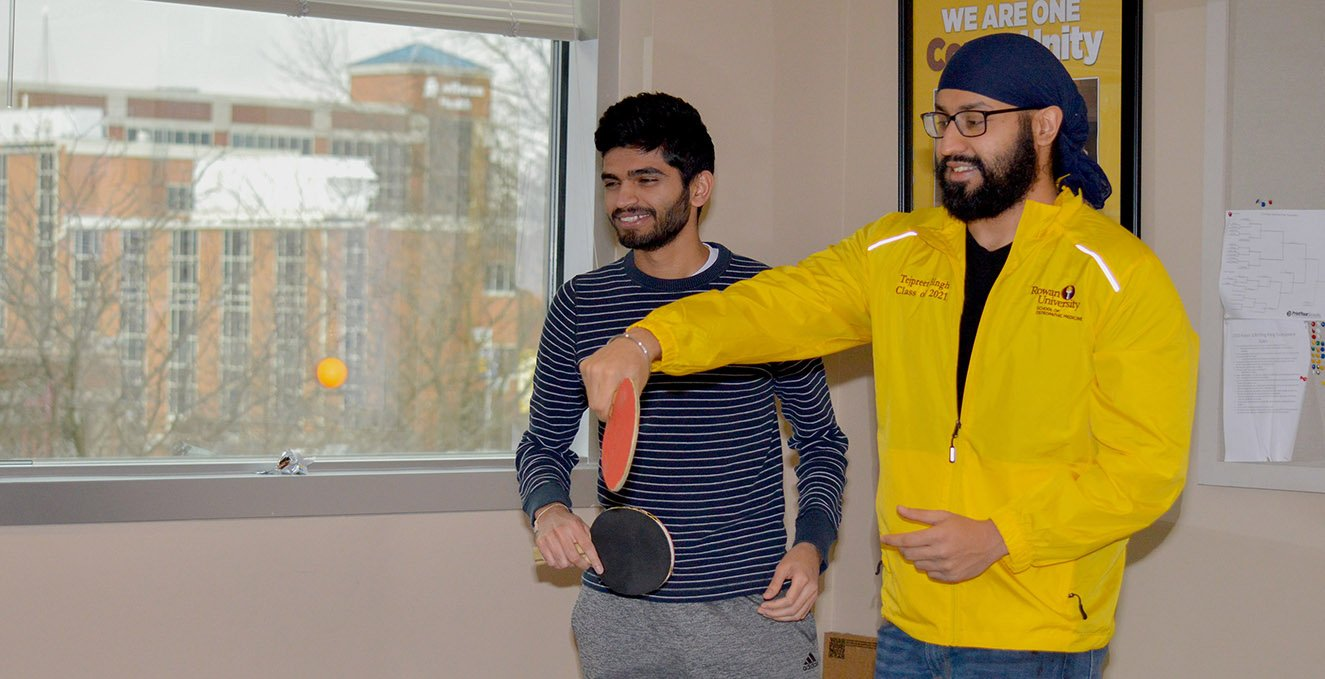 Two medical students play ping pong in the community room between classes.